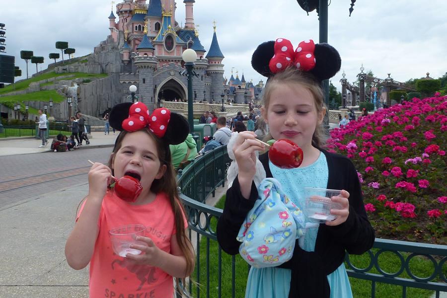 Kids eating toffee apples in front of Disneyland Paris Castle